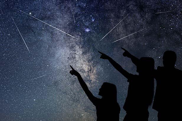 Menschen zeigen in Sternenhimmel bei Nacht